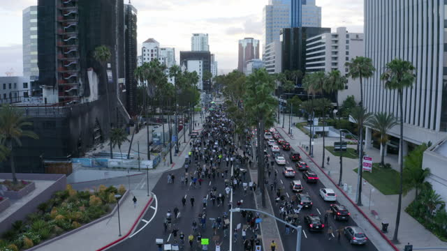rising aerial: enormous crowd of protesters with signs marches down major city street around cars with city scape - long beach, california - long beach california stock videos & royalty-free footage