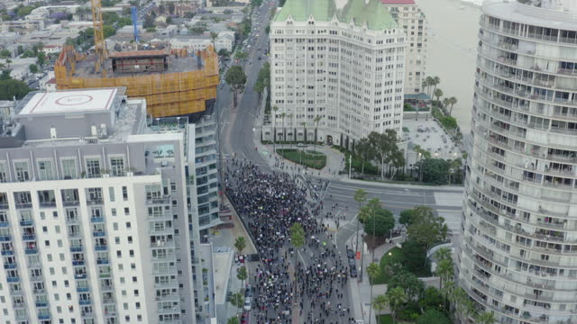 rising aerial: huge crowd of protesters meets at city crossroads with signs under tall apartment buildings near beach - long beach, california - protestor stock videos & royalty-free footage
