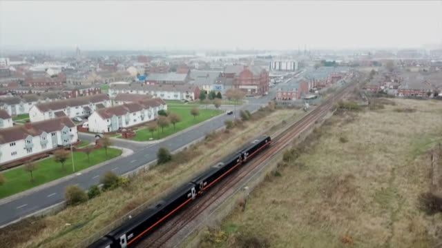 stockvideo's en b-roll-footage met rising aerial view of a train moving through hartlepool - county durham engeland
