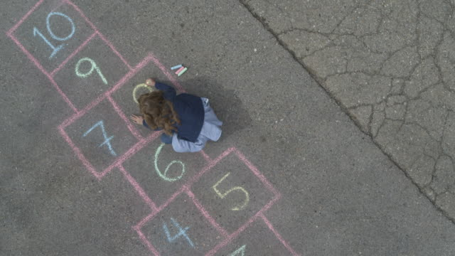 Rising aerial view of girl drawing hopscotch game in street then playing / Pleasant Grove, Utah, United States