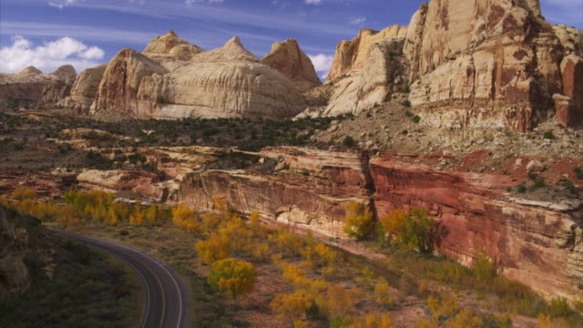 vídeos de stock, filmes e b-roll de rising aerial view of road near cliffs in remote desert / capitol reef, utah, united states - utah
