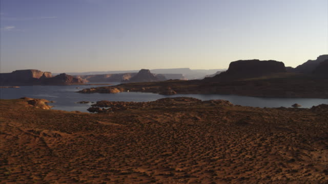 rising aerial view of rock formations and lake at sunset / lake powell, arizona, united states - lake powell stock videos & royalty-free footage