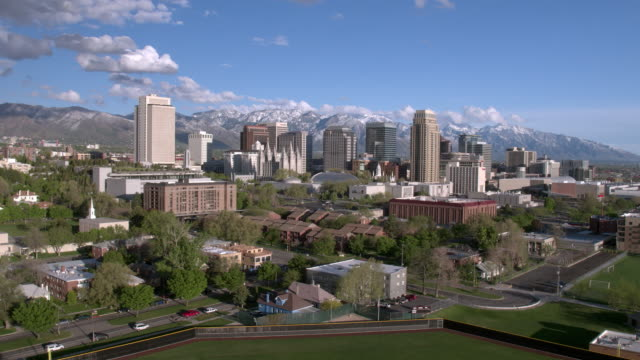 Rising aerial view of Salt Lake City against the Wasatch Mountains