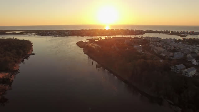 drone. rising aerial view of serene sunrise at snows cut canal and luxury beach houses at carolina beach - carolina beach stock videos and b-roll footage