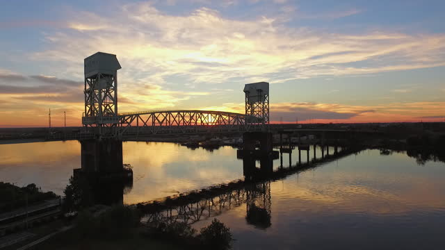 vídeos de stock, filmes e b-roll de drone. rising aerial view of the cape fear memorial bridge as cars drive over during majestic sunset - wilmington carolina do norte