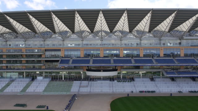 rising aerial view of the new grandstand and royal box at ascot racecourse - captured by a licensed uav operator with pfaw - イギリス アスコット競馬場点の映像素材/bロール