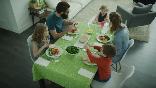 rising crane shot of family eating spaghetti at dinner table / lehi, utah, united states - family with three children stock videos & royalty-free footage