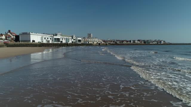 rising drone shot from the water at bridlington beach - bridlington stock-videos und b-roll-filmmaterial
