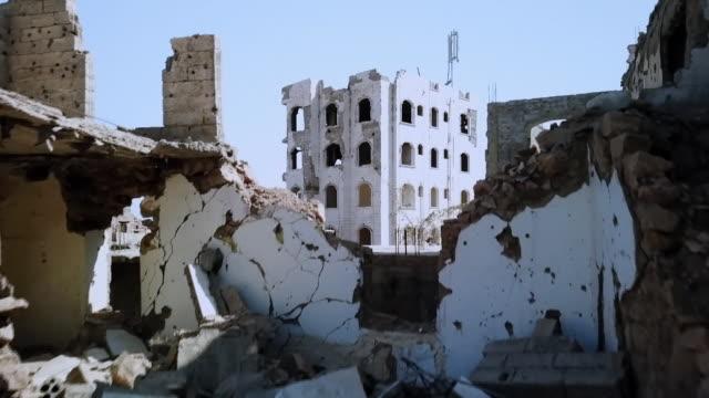 vidéos et rushes de rising drone shot of bombed-out buildings in taiz, yemen - bombardement