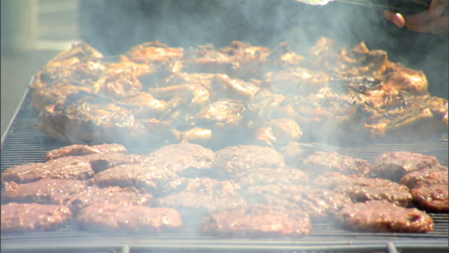 rising from grill fg, hamburger patties & half chickens grilling on grill, unidentifiable person turning over chickens w/ food clamp. bbq, barbecue,... - クランプ点の映像素材/bロール