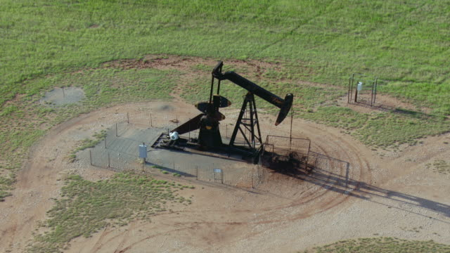 rising shot of pumpjack at oil well - oklahoma stock-videos und b-roll-filmmaterial
