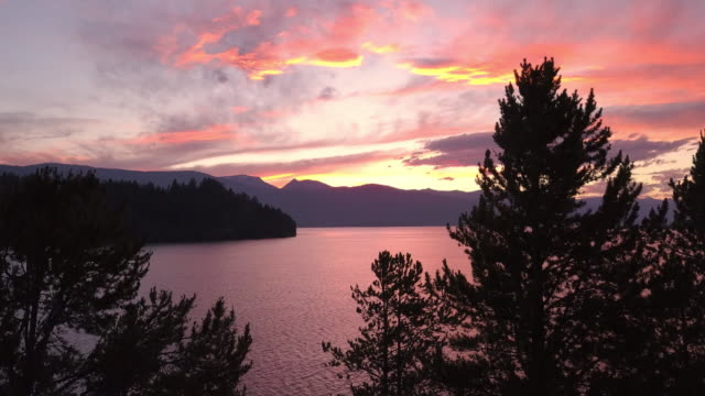 vidéos et rushes de rising slowly over trees viewing colorful sunset over lake - montana