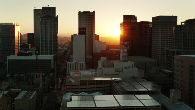 rising sun appearing between downtown phoenix skyscrapers - arizona stock videos & royalty-free footage