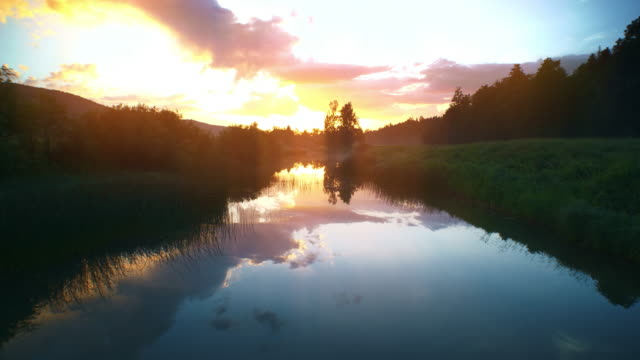 aerial rising sun painting the river surface in violet, blue and gold - slovenia meadow stock videos & royalty-free footage