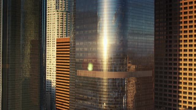 Rising Sun Reflected in Curved Glass Office Tower - Aerial