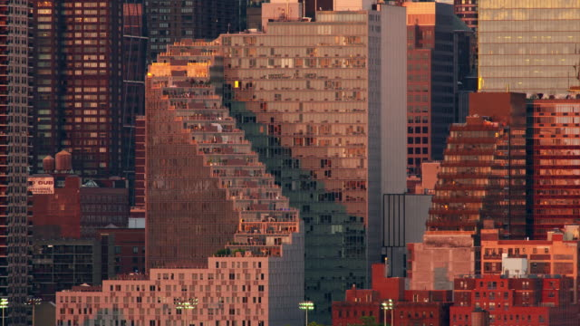 rising sun reflects off a single window of the mercedes house in new york city's hell's kitchen. - campo totale video stock e b–roll