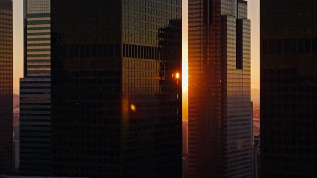 vidéos et rushes de soleil levant brillant entre les gratte-ciel de district financier de los angeles - drone shot - matin