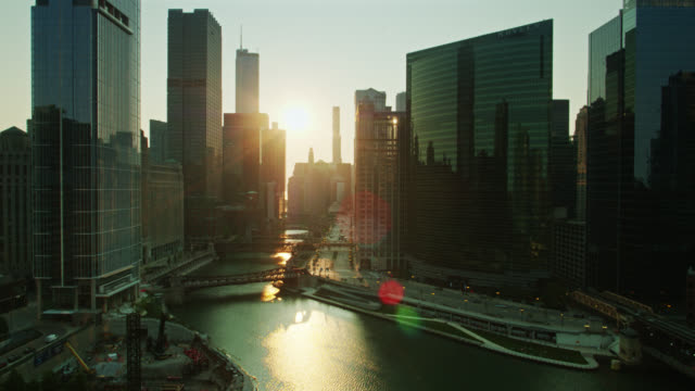 rising sun shining down chicago river - aerial - willis tower stock videos & royalty-free footage