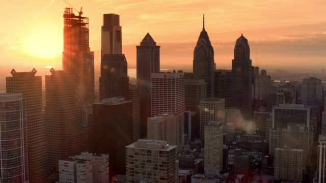 aerial rising sun shining on the skyscrapers of the center city in philadelphia, pa - ペンシルベニア州点の映像素材/bロール