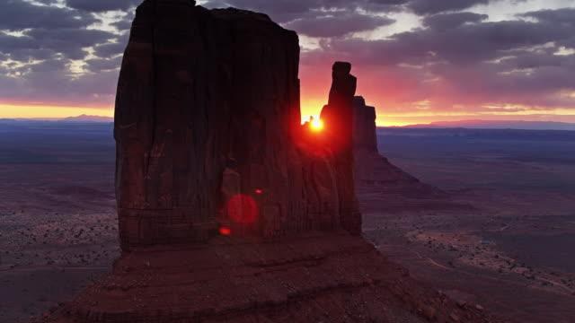 vídeos de stock, filmes e b-roll de sol de aumentação que brilha através do vale do monumento mitten buttes-aéreo - mitten