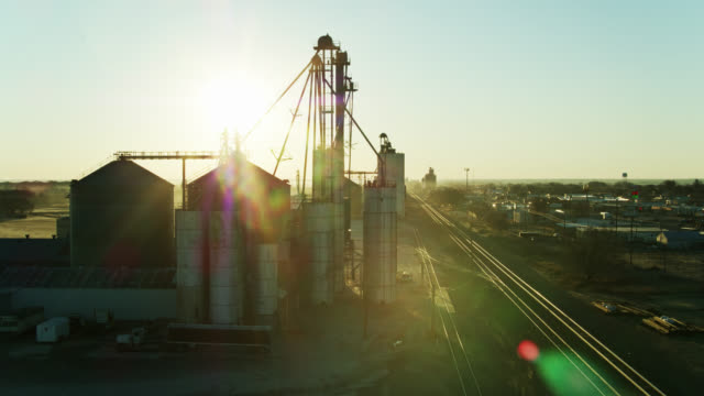 rising sunlight shining on train tracks and grain silos - drone shot - freight transportation stock videos & royalty-free footage