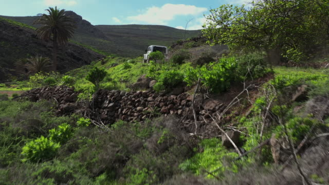 vidéos et rushes de rising up aerial shot showing an off-road vehicle driving through a rural, volcanic landscape, lanzarote, spain - paysage extrême