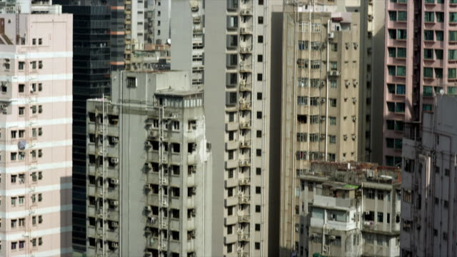 rising vertical shots of large high rise buildings in hong kong - population explosion stock videos & royalty-free footage
