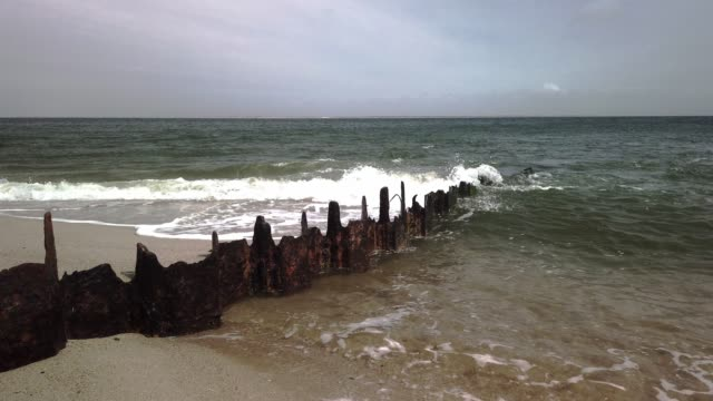 stockvideo's en b-roll-footage met risk of death: dangerous remains of groynes on the beach of sylt - tina terras michael walter