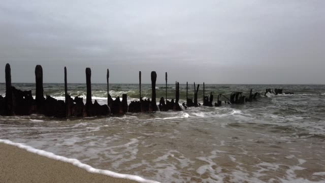 risk of death: dangerous remains of groynes on the beach of sylt - tina terras michael walter stock-videos und b-roll-filmmaterial