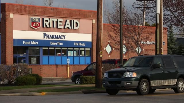 A Rite Aid pharmacy stands in Akron Ohio US on Thursday April 7 2016 Shots shot between two parked cars of Rite Aid Exterior with signage above Rite...