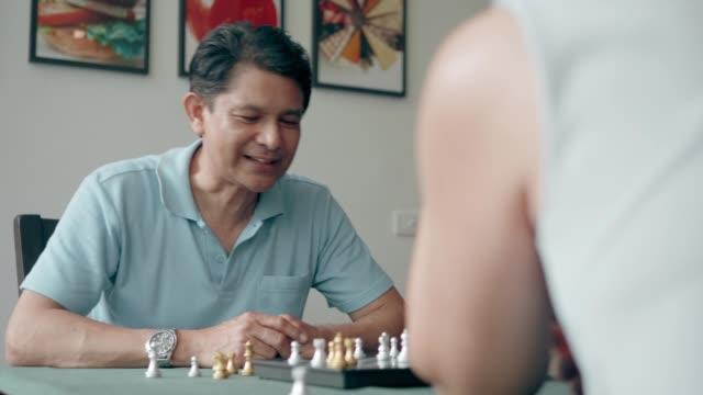 vídeos y material grabado en eventos de stock de rivalidad ajedrez: pareja mayor tratando de jugar al ajedrez para la relajación en casa - enfermedad de alzheimer