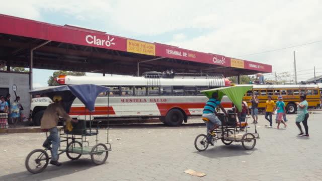 Rivas Nicaragua bus station establishing shot / b-roll. Local people, travelers and rickshaw bikes crossing.