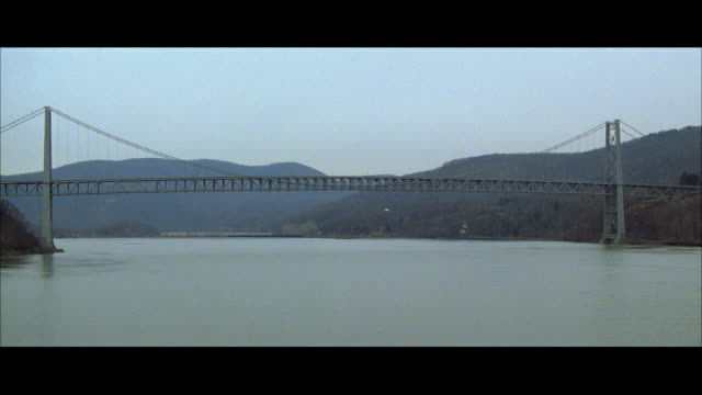 aerial ws tu pan ts river and car crossing bridge - レターボックス点の映像素材/bロール