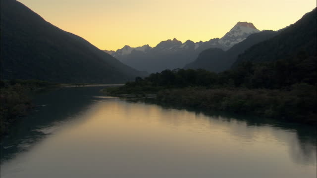LOW AERIAL, River and mountains at sunset, Fiordland National Park, New Zealand