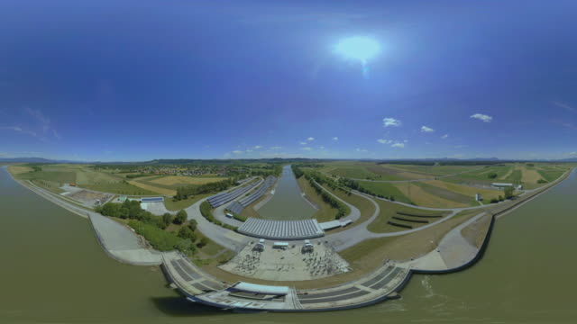 AERIAL VR 360: River bed at a hydropower plant with solar arrays on the banks of the river