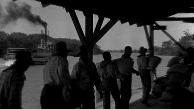 dx - river boat - from dock - a sternwheeler in from l - moves r - continuation - pan about - the boat along r - pick up dock and black stevedores - b&w. - docker stock videos & royalty-free footage