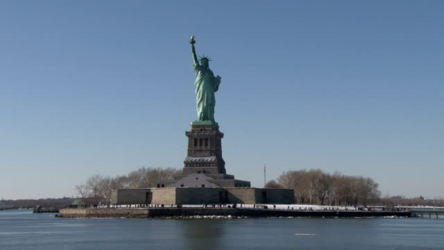 river boat sails past the statue of liberty on a cold winter day. no audio - freiheitsstatue stock-videos und b-roll-filmmaterial