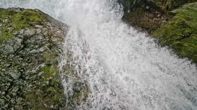 slo mo river caught in a rocky river bed flowing over the rocks creating a beautiful waterfall - waterfall stock videos & royalty-free footage