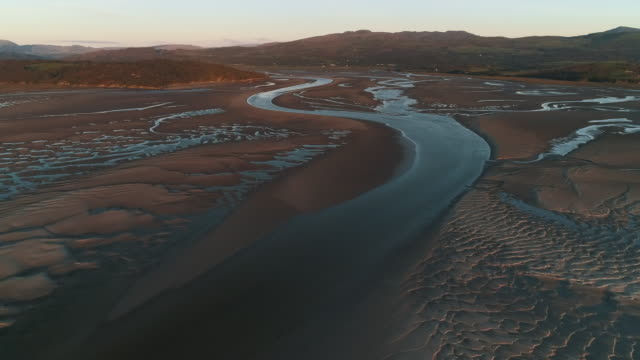 river channel in an estuary at low tide filmed by drone, borth-y-gest, wales, united kingdom - low tide stock videos & royalty-free footage
