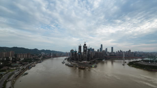 tl ws ha river city dawn to dusk transition featuring construction cranes swinging / chongqing, china - raffles city stock videos & royalty-free footage
