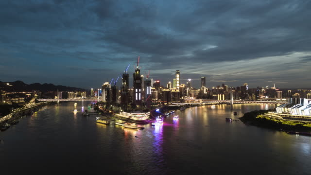 tl ws ha river city dusk to night transition featuring construction cranes swinging / chongqing, china - raffles city stock videos & royalty-free footage