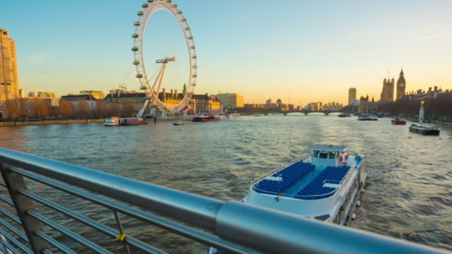 river cruise boat on river thames and london skyline at sunset. - 遊覧船点の映像素材/bロール