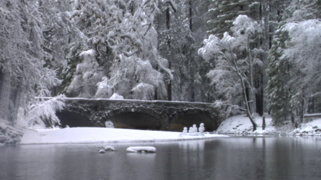 WS River flowing near footbridge, small snowmen and snow-covered trees in Yosemite National Park / California, USA