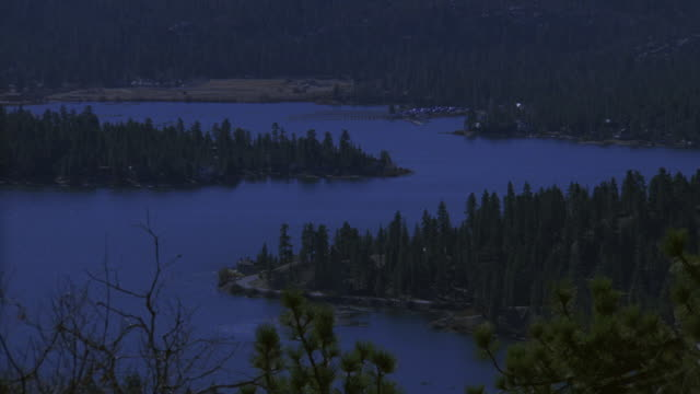 vidéos et rushes de pan river flowing through forested area glowing from moonlight - vue latérale