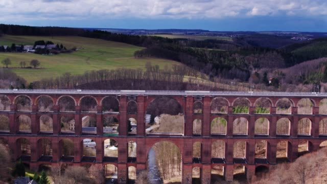 river flowing under göltzsch viaduct - drone shot - colonna architettonica video stock e b–roll