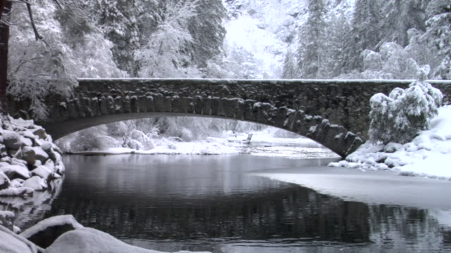 ws river flowing under stone footbridge near snow-covered trees in yosemite national park / california, usa - yosemite national park stock videos and b-roll footage