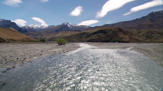 stockvideo's en b-roll-footage met a river flows over a stony bed toward snowy mountains. available in hd. - geërodeerd