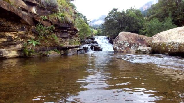 vidéos et rushes de la rivière coule sur les rochers dans une belle piscine rocheuse dans les montagnes du drakensberg - parc national
