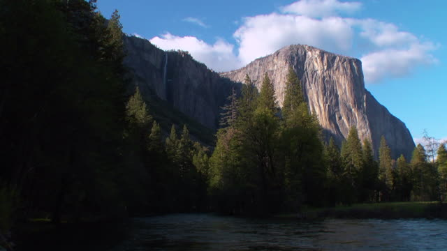 a river flows past mountains in yosemite national park. - エルキャピタン点の映像素材/bロール