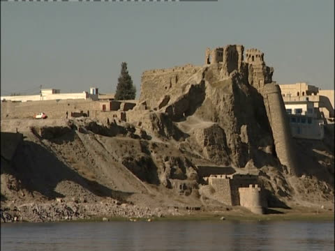 A river flows past the Bash Tapia castle ruins in Mosul, Iraq.